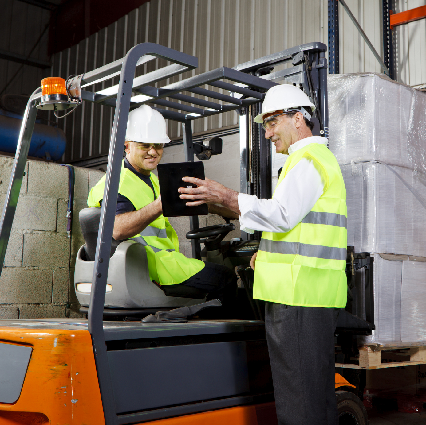 Two men wearing safety gear working in a warehouse with a forklit. One man showing the other information on a digital tablet.